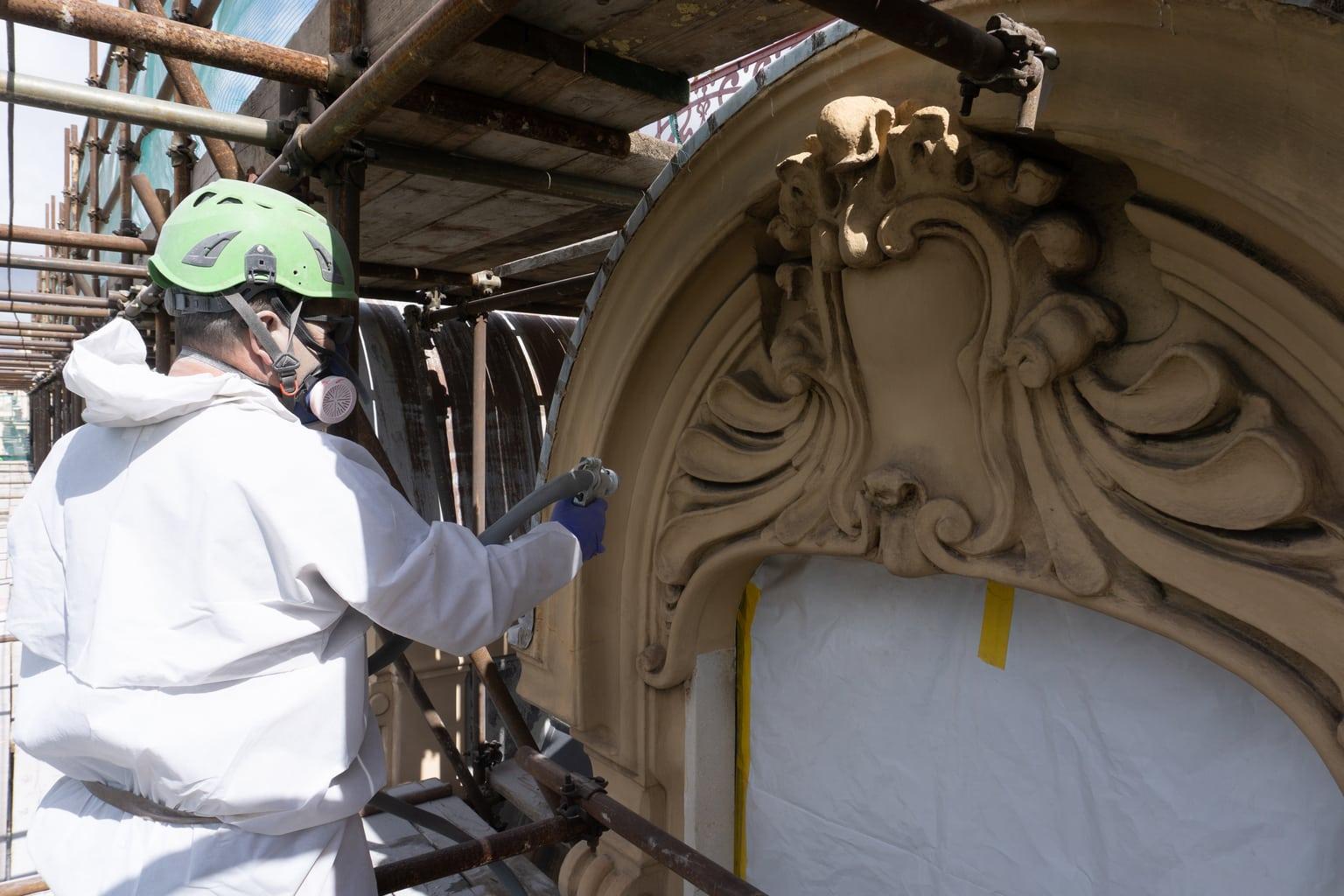 Operai ripuliscono la facciata di un palazzo storico